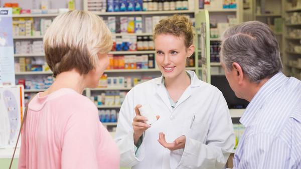 Pharmacist talking to man and woman