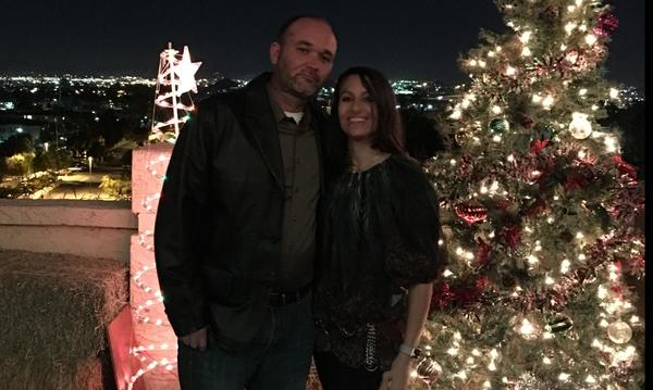 A man and woman posing next to a Christmas tree, with a cityscape in the background.
