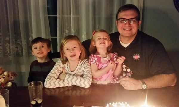 A man with three children in front of a birthday cake.