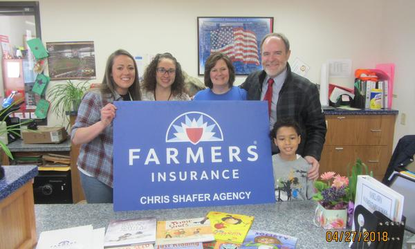 Four adults and a child posing with a Farmers sign.