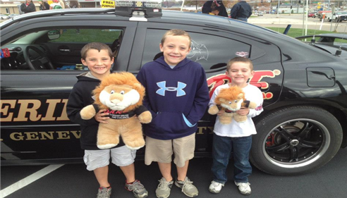 3 young boys pose with stuffed animals in front of a car