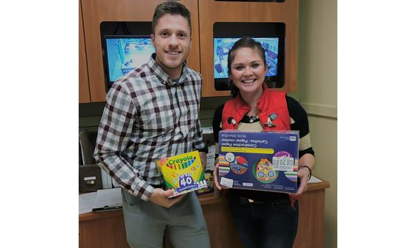 Agent and woman holding school supplies