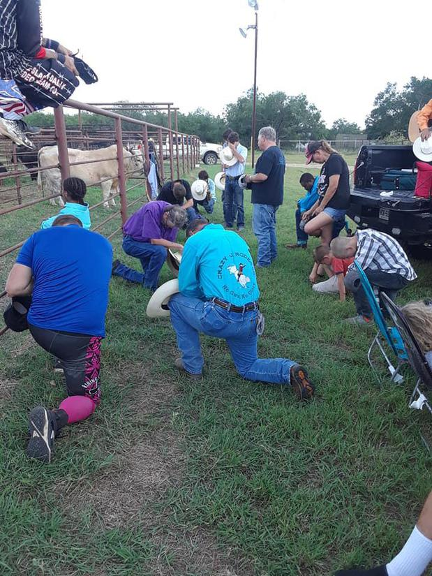 four bull riders down on one knee praying