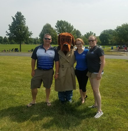 An outside group photo of the Curtis Agency with a dog character at a pet show.