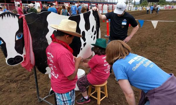 A group of children and adults learning how to milk a cow.
