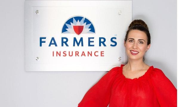 Woman standing in front of a Farmers Insurance® banner