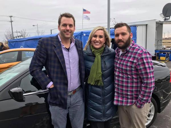 three adults standing in front of car
