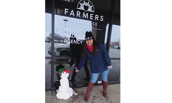 Someone poses in front of a Farmers office with a snowman