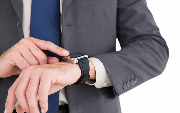 Person looking at his wearable smart watch at the workplace