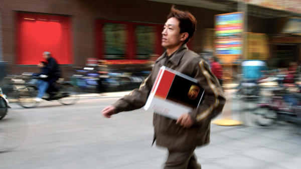 UPS courier carrying a package down a busy street
