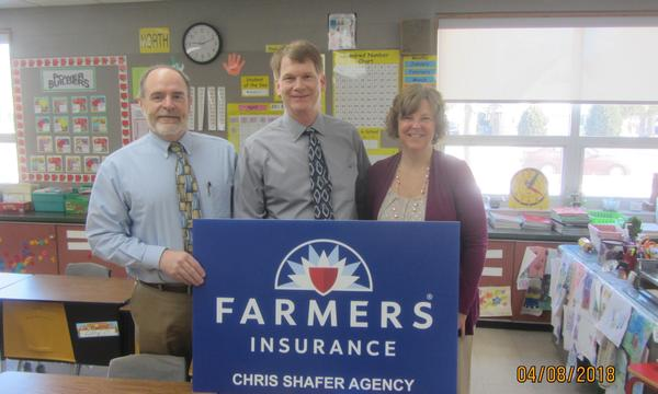 Three adults posing with a Farmers sign.