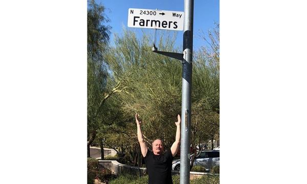 "Agent standing beneath a street sign that says ""Farmers Way"""