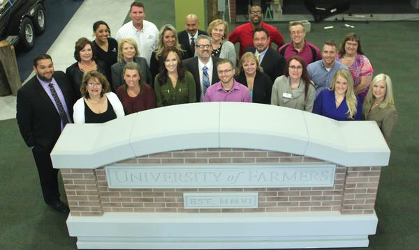 Group of Farmers Insurance agents posing for a group photo behind the Farmers University sign.