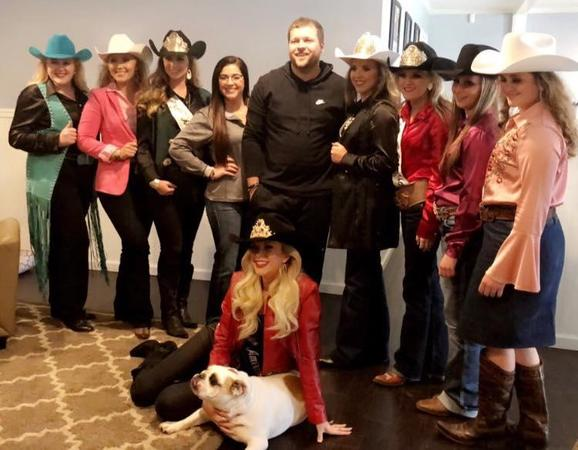A group photo of the Brown agency wearing cowboy hats and with a dog.