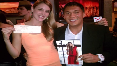 Agent Manuel Baniago standing with a woman who is featured on the cover of a magazine.