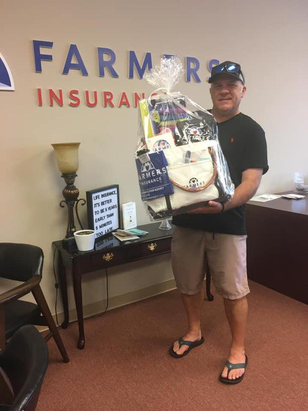 man holding gift basket in front of farmers sign