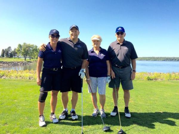 Four people standing on a golf course