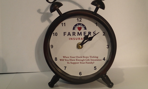 An alarm clock with the Farmers Insurance logo on its face