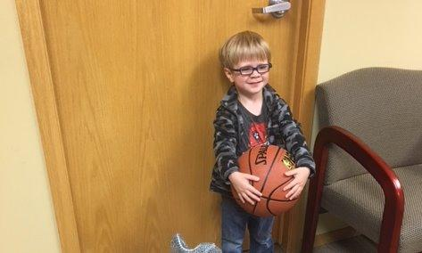Child poses with basketball.