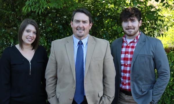 Agent Thomas Cargle with his male and female staff members standing in front of a bush.