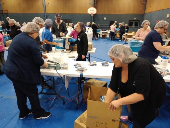 volunteers preparing food boxes for local charity called Feed my starving children