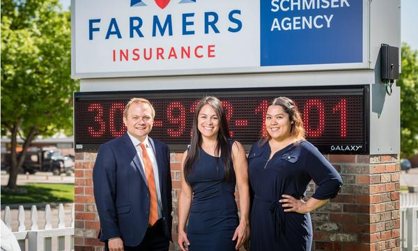 Agent Mike and two female staff members posing outside the agency's sign.