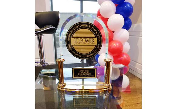 Farmers Insurance J.D. Power Award on a desk with balloons in the background.