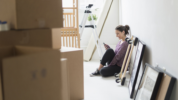 Young female homebuyer sitting on floor surrounded by moving boxes looking at cell phone