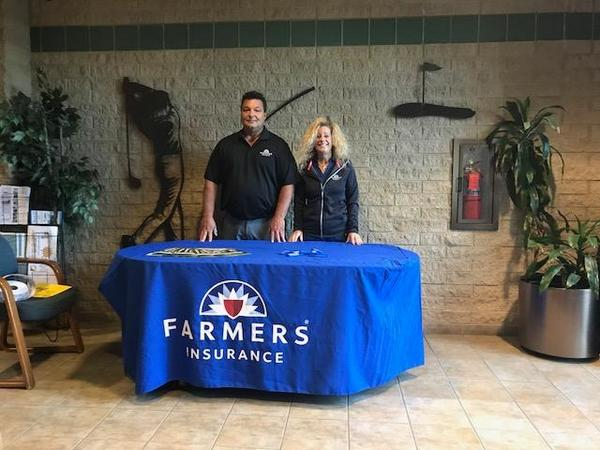Two people standing behind a Farmers table
