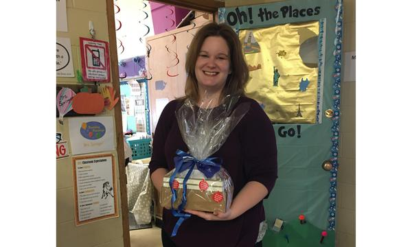 teacher at montini middle school holding a gift basket