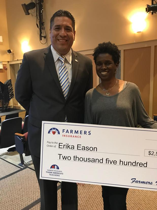 Man and woman standing with large check