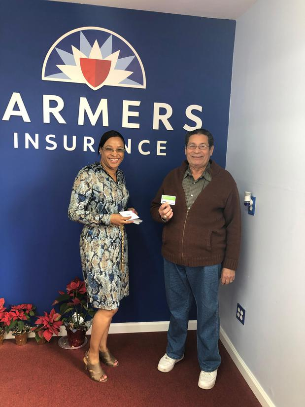 Woman and man standing in front of Farmers® Insurance logo