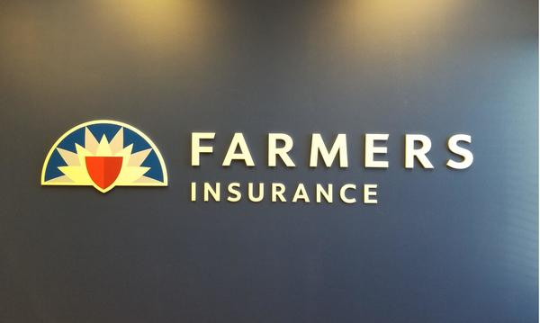 The Farmers Insurance logo on a blue wall.