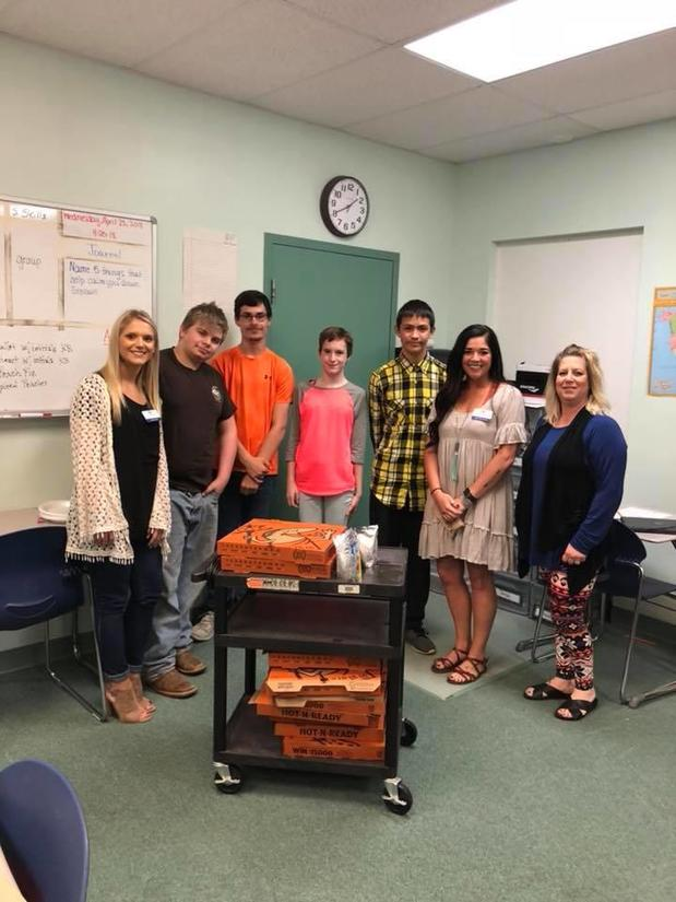 A photo of agent Demi Gurkin with children of the Cabot Learning Academy. Posing behind a cart holding many pizza boxes.