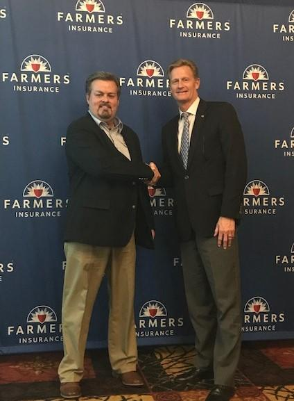 Two people posing in front of background of Farmers logos