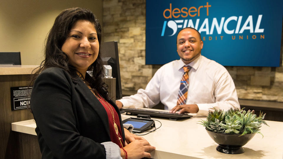 Desert Financial teller helping a customer in a branch.