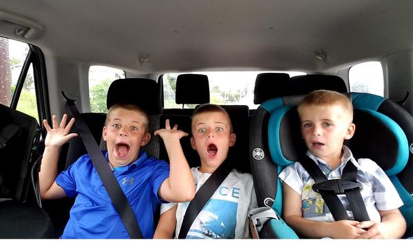 3 children in the back seat of a car, making funny faces at the camera.