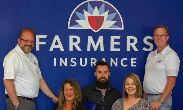 Agent Victor Thompson and his staff of two men and two women, in front of the Farmers logo.