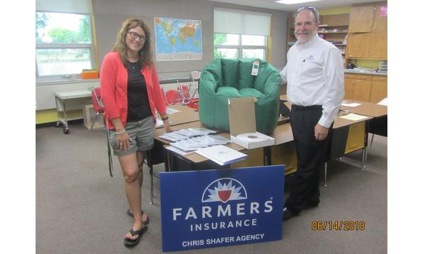 Agent Chris Shafer standing with a female teacher next to the Farmers Insurance logo and a new chair for the classroom.